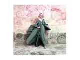 Pose Against a Mural of Swirling Roses  Model Wearing Blue Float of Peignoir in Blue Nylon Yarn