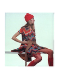Model  Sitting on White Slat  Wears Bright Red and Blue Aztec-Print Sleeveless Coat