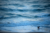 A Couple Plays in the Ocean Waves at Dusk at Riviera Beach