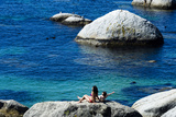 A Couple Sunbathing on a Boulder Above a Clear Blue Sea