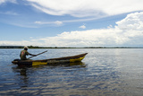 A Fisherman Paddling a Canoe on a Wide African River