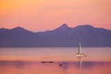 A Sailboat in Lake Villarrica's Flat Calm Water with Small Ripples  at Sunset