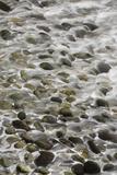 Surf Runs Through Stones on a Beach