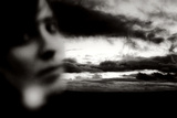Young Woman Out of Focus in Front of Cloudy Sky Looking into the Camera