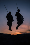 Two Masaai Warriors Silhouetted Performing Traditional Jump - Leap Kopje at Sunset