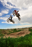 Two Riders Jump in Unison at a Motocross Event